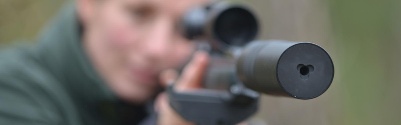 Jägerin mit Schalldämpfer auf Jagdwaffe